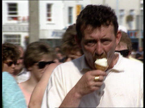 vídeos de stock e filmes b-roll de monopoly inquiry; c5l: u'lay lib england: yorkshire: scarborough: ext cms man along eating ice cream cornet followed by woman ditto lib london:... - scarborough reino unido