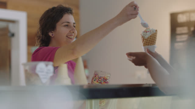 vidéos et rushes de ice cream shop employee adds multi colored sprinkles to a woman's ice cream cone - choisir