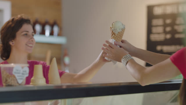 ice cream shop employee gives an ice cream over to two young friends - opening event stock videos & royalty-free footage