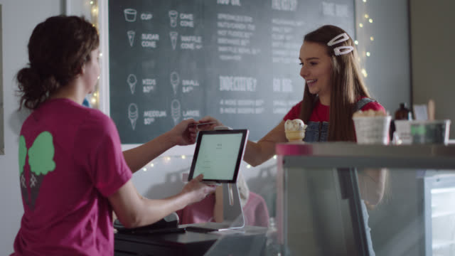 ice cream shop employee runs a credit card payment on a tablet for a female customer - kreditkarte oder kontokarte stock-videos und b-roll-filmmaterial