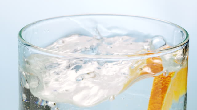 Ice cube and orange slice falling down in water glass