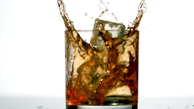 Ice cube falling in whiskey tumbler