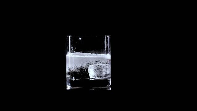 ice cube falling into fizzy water in drinking glass - carbonated stock videos & royalty-free footage