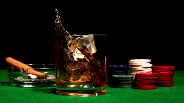 vídeos y material grabado en eventos de stock de ice cube falling en el vaso de whisky en mesa del casino - vaso