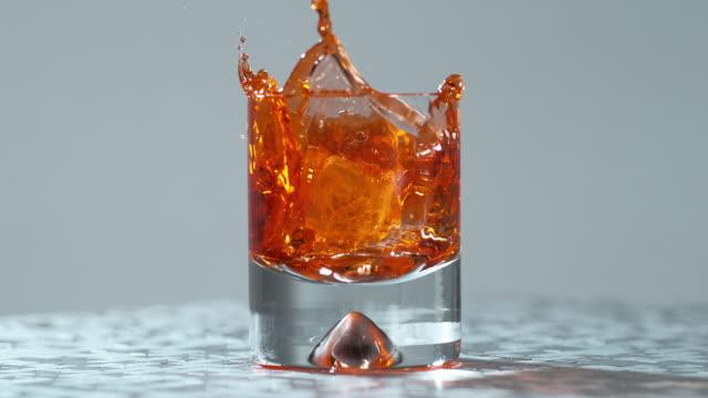 vidéos et rushes de ice cube splashes in a glass with liquor / slow motion - glaçon