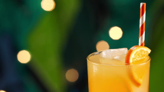 ice cube splashing in tropical orange drink - tropical drink stock videos & royalty-free footage
