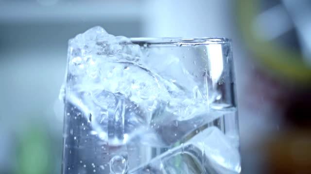 vídeos de stock, filmes e b-roll de cubo de gelo caindo na água gaseificada - gelo