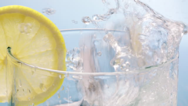 ice cubes falling down in water glass decorated with lemon slice - cachaça stock videos & royalty-free footage