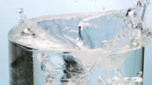 Ice cubes falling down into water glass