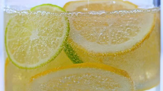 slo mo ld cubetti di ghiaccio che cadono in un bicchiere di acqua frizzante - cubetto di ghiaccio video stock e b–roll