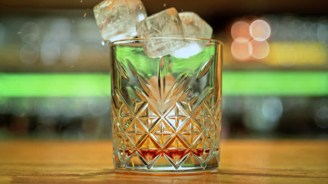 vídeos y material grabado en eventos de stock de slo mo ds cubos de hielo cayendo en un vaso con licor - plano de plataforma rodante