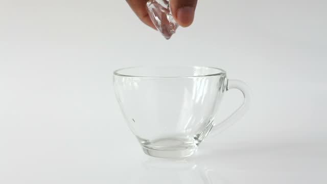 Ice cubes falling into cup