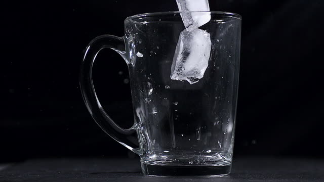 ms slo mo ice cubes falling into glass against black background / vieux pont, normandy, france  - drinking glass stock videos & royalty-free footage
