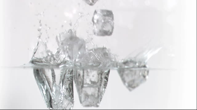 Ice cubes falling in super slow motion into water