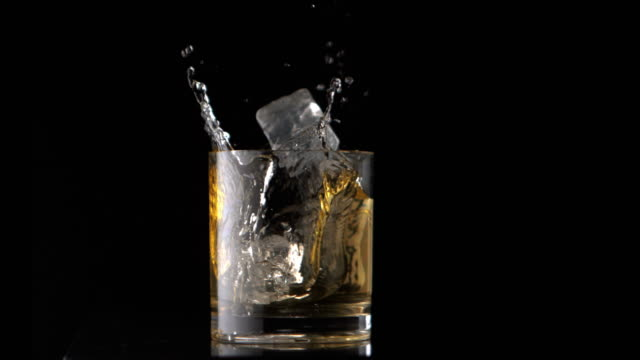 Ice cubes falling into whiskey