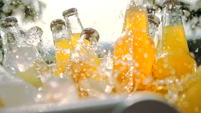 super slo mo ice cubes falling over bottles of soft drinks in a cooler - cooler container stock videos & royalty-free footage