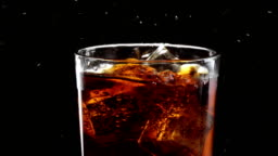 Ice cubes float in a glass of refreshing cola