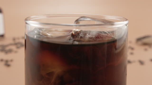 ice cubes floating in a glass of cold brew coffee - table top shot stock videos & royalty-free footage