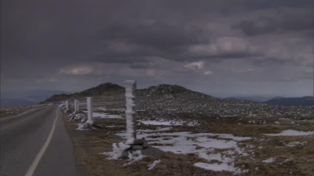 vídeos y material grabado en eventos de stock de ice encrusted posts stand along a road that runs through a rocky, open plain. - poste de madera