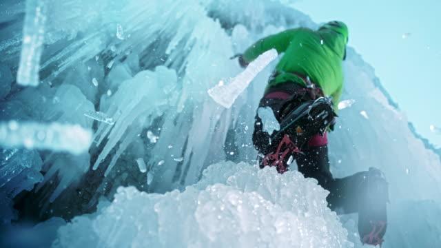 vídeos de stock e filmes b-roll de slo mo ice falling as climber uses the axe - desporto radical