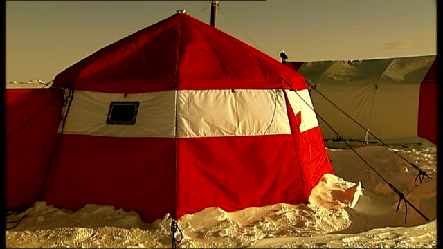 Ice field at sunset Lab tent on ice base and scientists seen through window of tent Sun setting on snow covered landscape