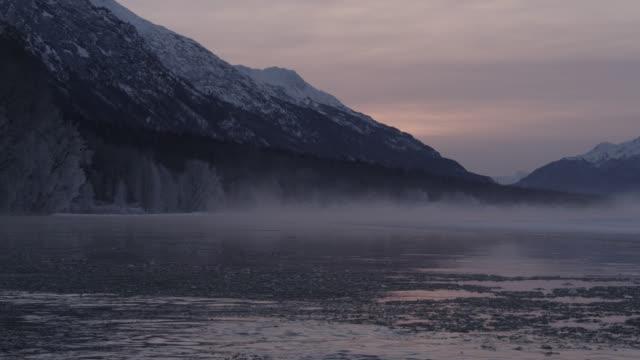 vídeos de stock, filmes e b-roll de ice floats down misty river at sunrise, alaska, usa - snowcapped mountain