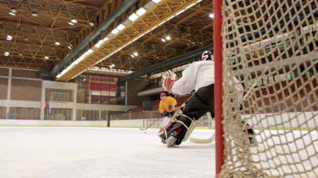Ice hockey goalie defending his goal while offensive player is taking a shot and scoring during the game in a rink.