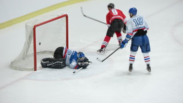 ice hockey goaltender unsuccessful in net defense - アイスホッケー点の映像素材/bロール