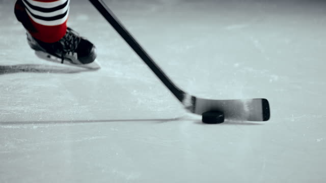 SLO MO Ice hockey player hitting the puck with a stick