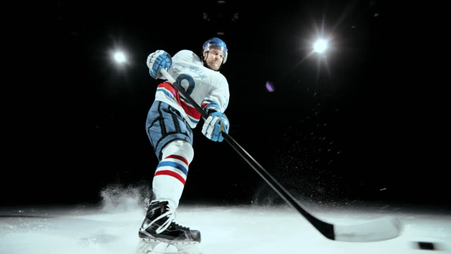 slo mo ice hockey player making the shot - アイスホッケー点の映像素材/bロール