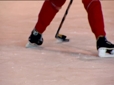 Ice hockey player skates towards goal keeper whacks puck into net and skates off Moscow