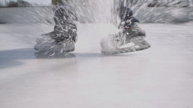 MS Ice hockey player skating toward camera, stopping in a slide and spraying camera with ice flakes / Long Island, NY