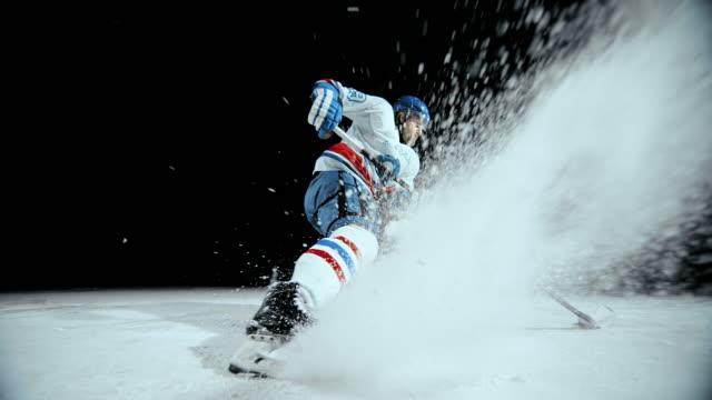 slo mo ice hockey player stopping and spraying ice particles - eis stock-videos und b-roll-filmmaterial