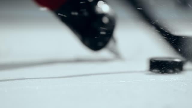 slo mo cu ice hockey stick striking the puck - アイスホッケー点の映像素材/bロール