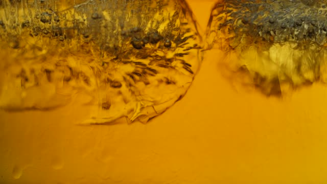 ice melting in whisky macro shot. - amber stock videos & royalty-free footage
