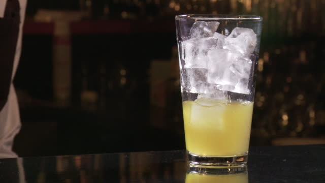 ice poured into cocktail as it's being made