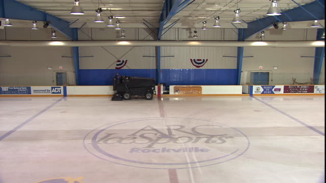 a ice resurfacing machine re-surfaces an ice rink. - アイススケート場点の映像素材/bロール