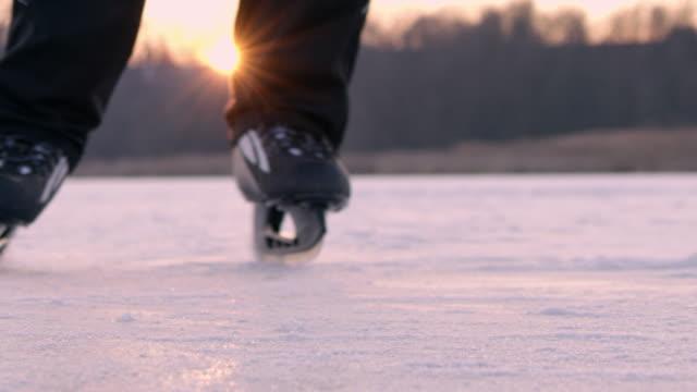 4K Ice skater sliding, spraying ice at camera, slow motion