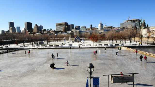 ice skaters on fresh polished ice rink in old port of montreal. extreme wide shot with montreal skyline in background - frozen stock videos & royalty-free footage