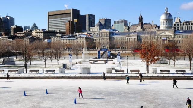 ice skaters on ice rink in old port of montreal. wide shot with montreal skyline in background - vieux montréal stock videos & royalty-free footage