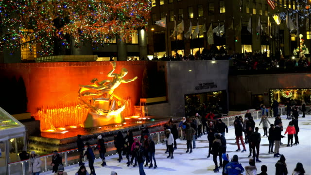 ice skating and looking at the rockefeller center christmas tree are a very popular tourist attraction / rockefeller center plaza midtown manhattan... - ロックフェラーセンターのクリスマスツリー点の映像素材/bロール