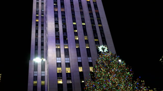 ice skating and looking at the rockefeller center christmas tree are a very popular tourist attraction / rockefeller center plaza midtown manhattan... - rockefeller center christmas tree stock videos & royalty-free footage