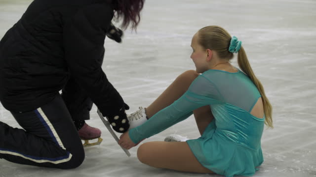 stockvideo's en b-roll-footage met ice skating coach helping young girl with ice skating injury - trainer