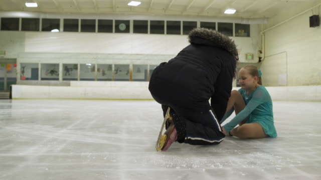 stockvideo's en b-roll-footage met ice skating coach helping young girl with ice skating injury. - trainer