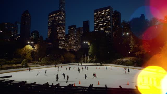 vídeos de stock e filmes b-roll de patinagem no gelo no central park com luzes de natal em primeiro plano - patinagem no gelo