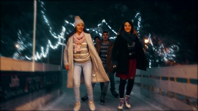 eislaufen in der eisbahn bei nacht - wintersport stock-videos und b-roll-filmmaterial
