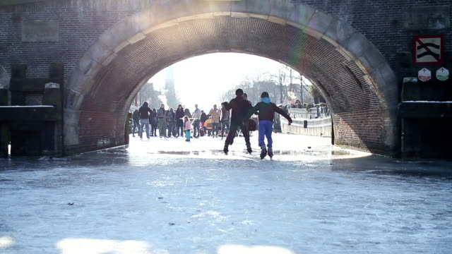 ice skating on frozen amsterdam canal under a bridge - ice skating stock videos & royalty-free footage