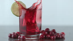 Ice splashing into cranberry juice in slow motion