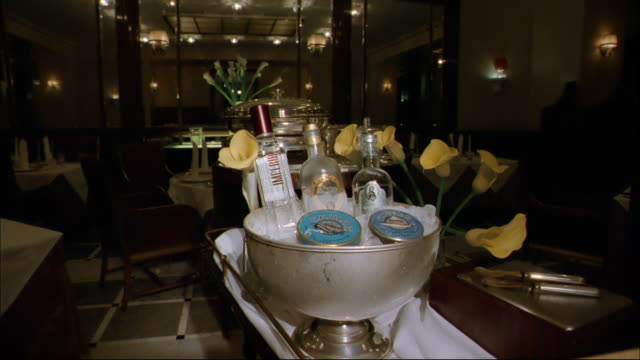 Ice surrounds three bottles of liquor and caviar in a bucket on a table in a restaurant.
