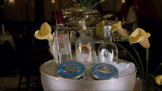 Ice surrounds three bottles of liquor and caviar in a bucket.